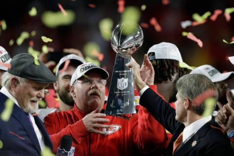El presidente de los Kansas City Chiefs, Clark Hunt, a la derecha, le entrega el trofeo al entr ...