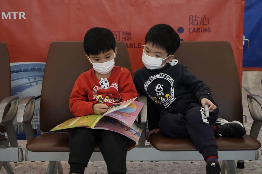 Pasajeros llevan máscaras para prevenir un brote del nuevo coronavirus en la estación de tren ...