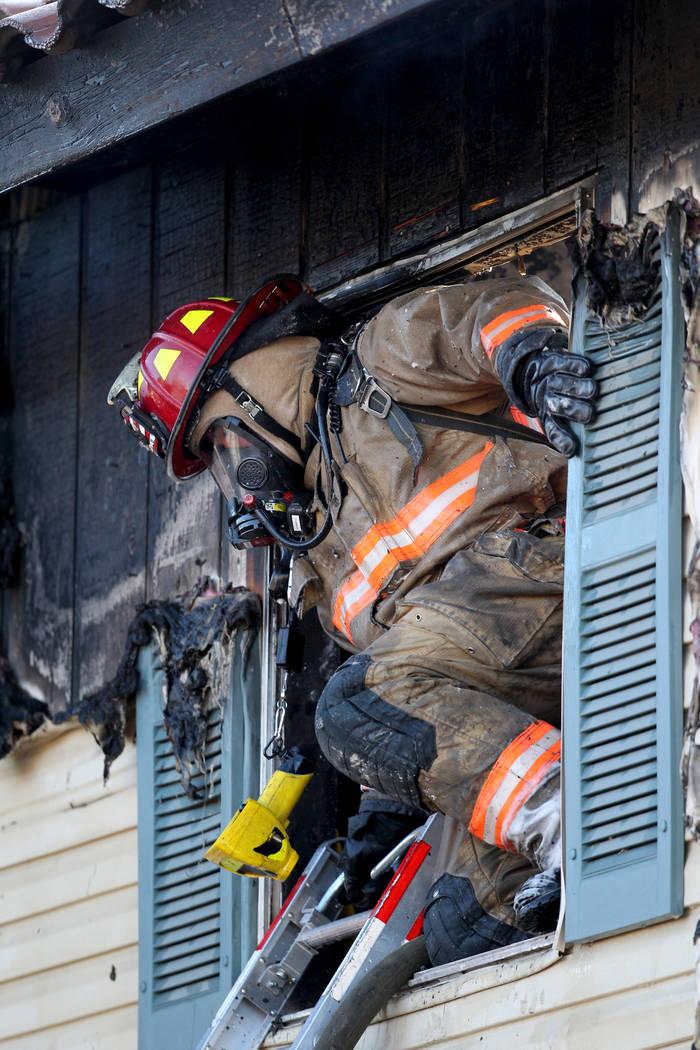 Un bombero sale por la ventana de un segundo piso mientras trabaja en los apartamentos Lantana ...
