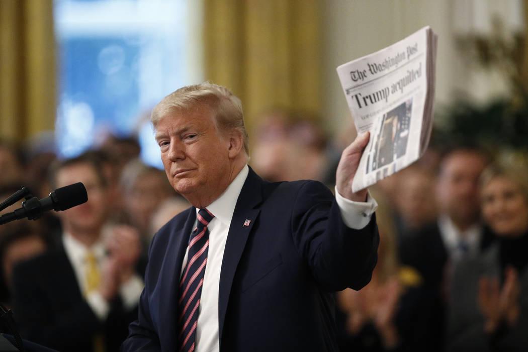 """El presidente Donald Trump sostiene un periódico con el titular que dice """"Trump absuelto"""" mien ..."""