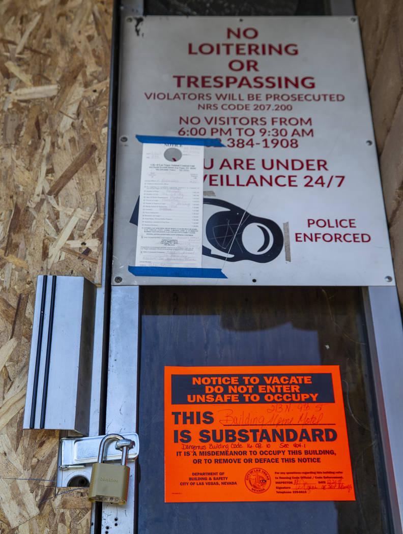 La puerta de entrada está cerrada con candado y marcada con un letrero de edificio peligroso e ...