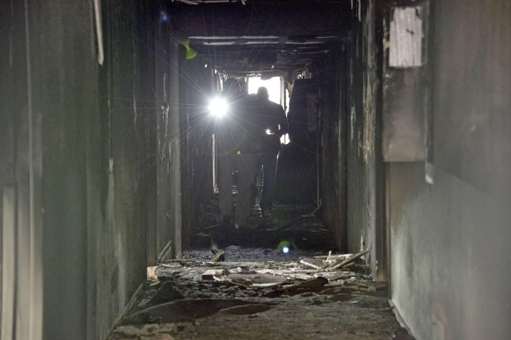 Los investigadores caminan por un pasillo interior después de un incendio en un complejo de ap ...