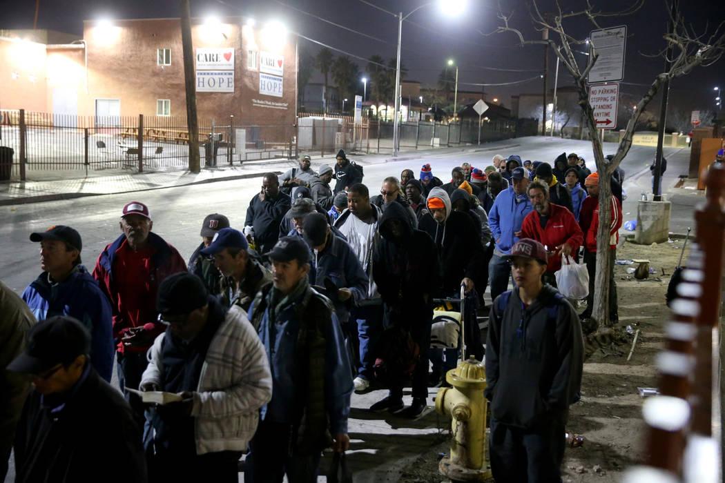 La gente se forma para solicitar las camas del refugio nocturno de Catholic Charities en Las Ve ...