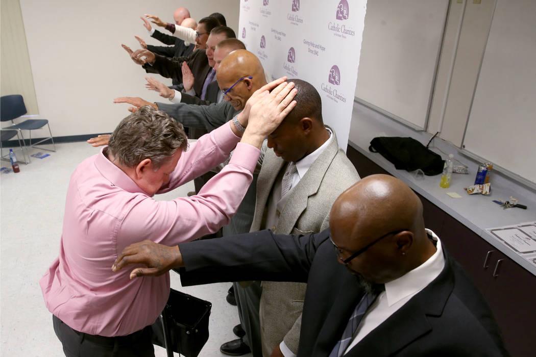 Michael Moore, segundo a la derecha, reza el diácono Tom Roberts y con sus compañeros durante ...