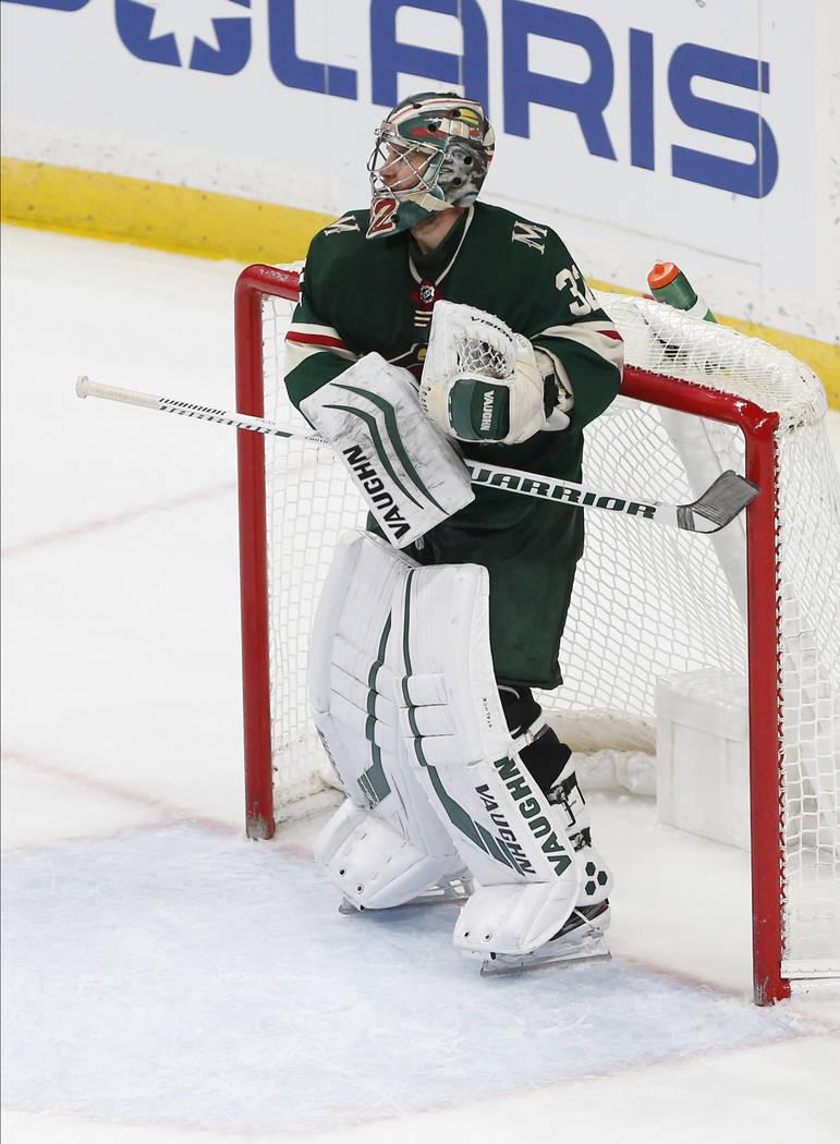 Alex Stalock de Minnesota Wild golpea su bastón de hockey contra el poste mientras celebra su ...