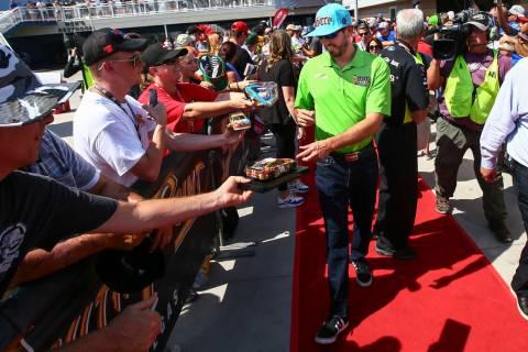Kyle Busch firma autógrafos a los aficionados antes de una carrera de autos de la Copa NASCAR ...