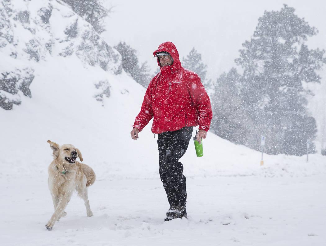 Paul Whitmoyer, a la derecha, y su golden retriever Kona caminando en la nieve en el Mount Char ...
