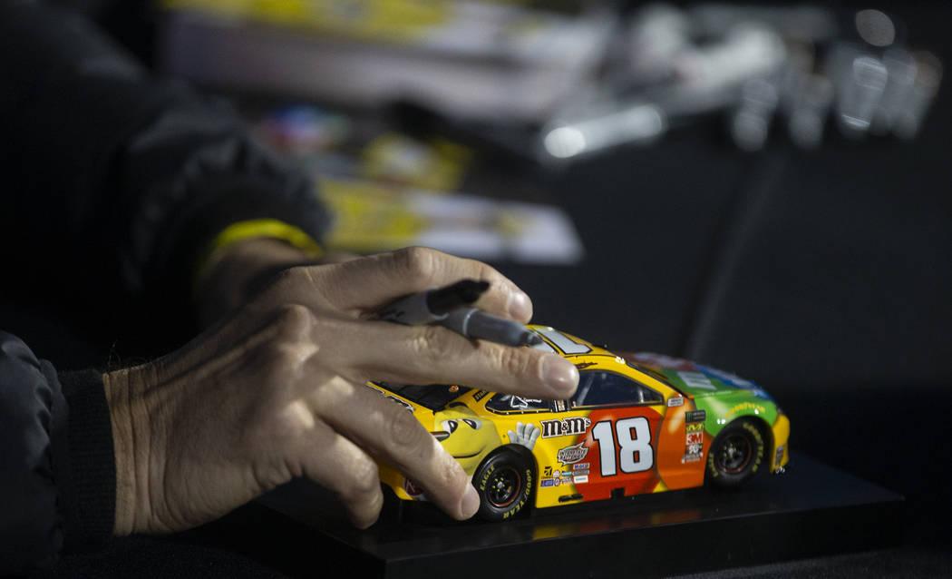 La estrella de la NASCAR, Kyle Busch, firma autógrafos antes del comienzo de la carrera Star N ...