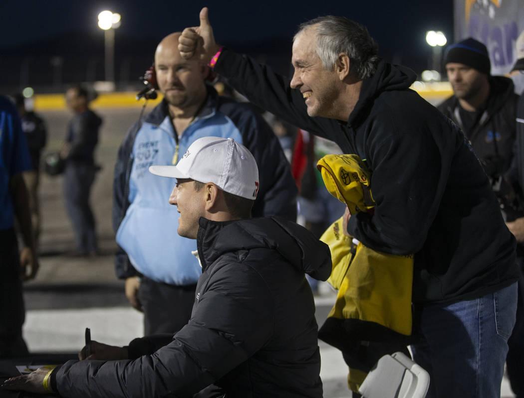 Lee McCreary, derecha, se toma una foto con la estrella de la NASCAR, Kyle Busch, antes del com ...