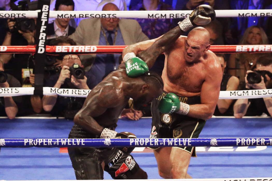 Tyson Fury, derecha, conecta con un gancho de derecha contra Deontay Wilder en el quinto asalto ...