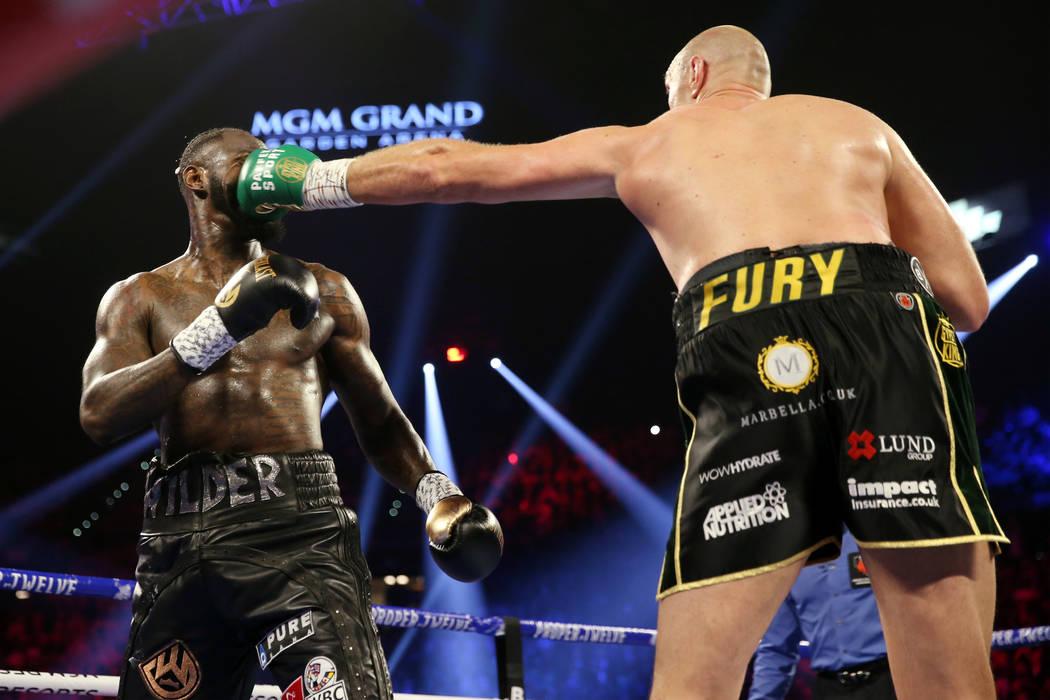 Tyson Fury, derecha, conecta un golpe contra Deontay Wilder en la segunda ronda del combate del ...