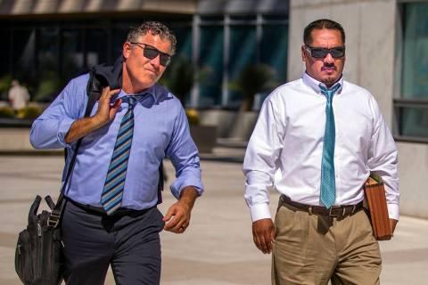 El abogado Mark Fleming, izquierda, camina con el acusado Albert López el 12 de agosto de 2019 ...