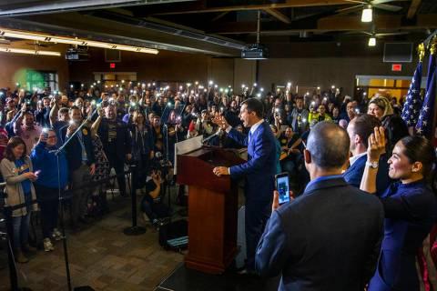 Miembros de la multitud sostienen sus teléfonos encendidos en apoyo al candidato presidencial ...
