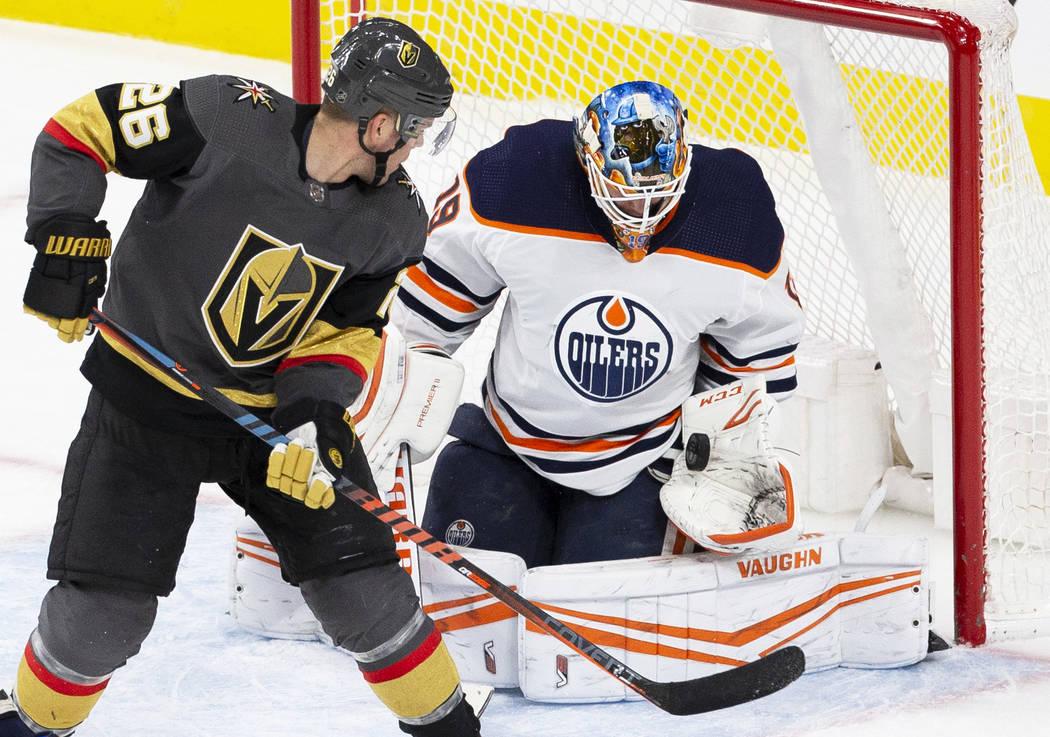 El portero de los Oilers de Edmonton, Mikko Koskinen (19), hace una atajada contra el centro de ...