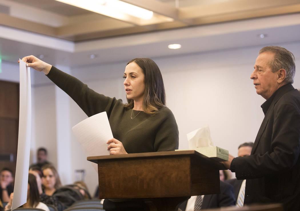 Allie Rossi, hermana de A.J. Rossi, sostiene una foto de A.J. mientras está de pie junto a su ...