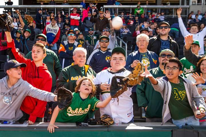 Los fans intentan atrapar una pelota lanzada por un jugador de los A's de Oakland durante un pa ...