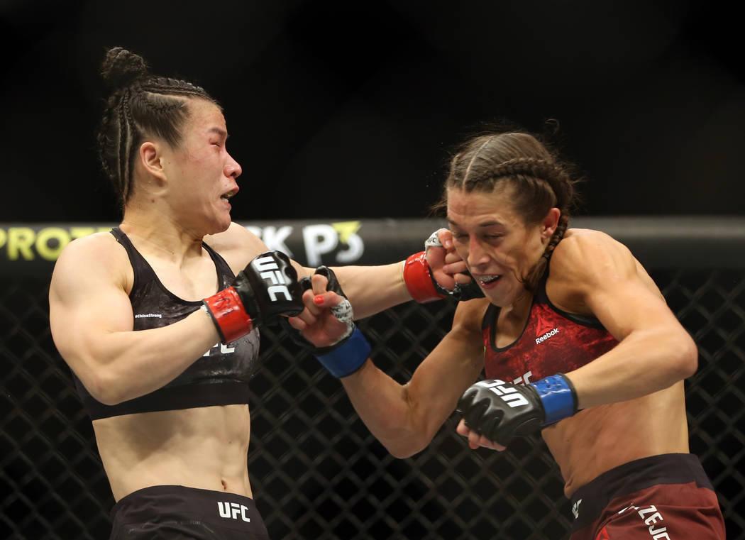 El peso paja femenino Weili Zhang, a la izquierda, se conecta con un golpe a Joanna Jedrzejczyk ...