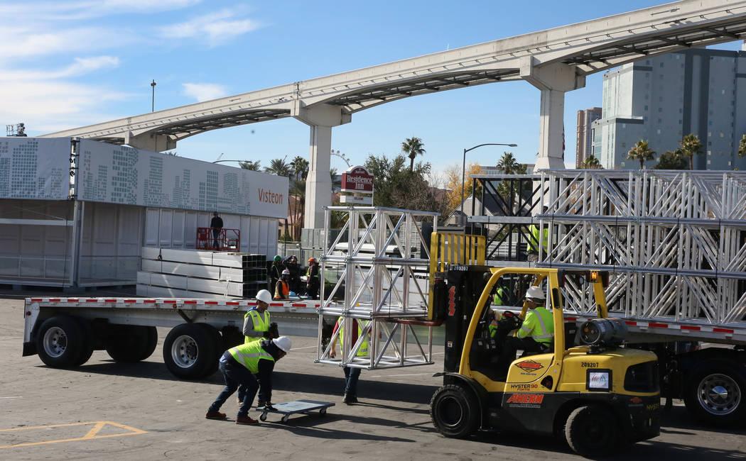 Trabajadores de Pavillon Event Service descargan equipos de construcción junto al stand de Vis ...