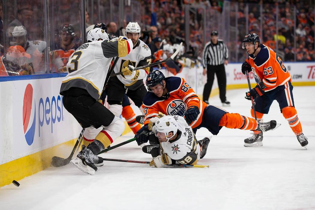 Matt Benning (83) de los Oilers de Edmonton cae sobre William Carrier (28) de los Golden Knight ...
