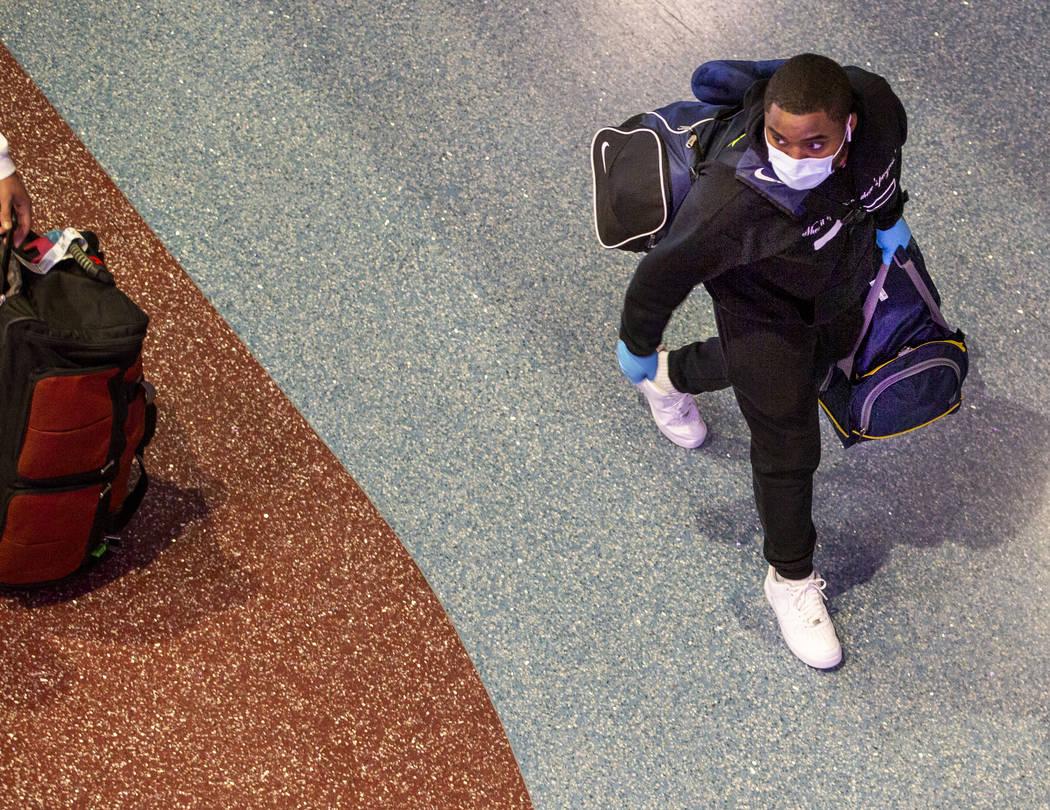 Un pasajero usa una máscara facial mientras camina por la Terminal 1 del aeropuerto internacio ...