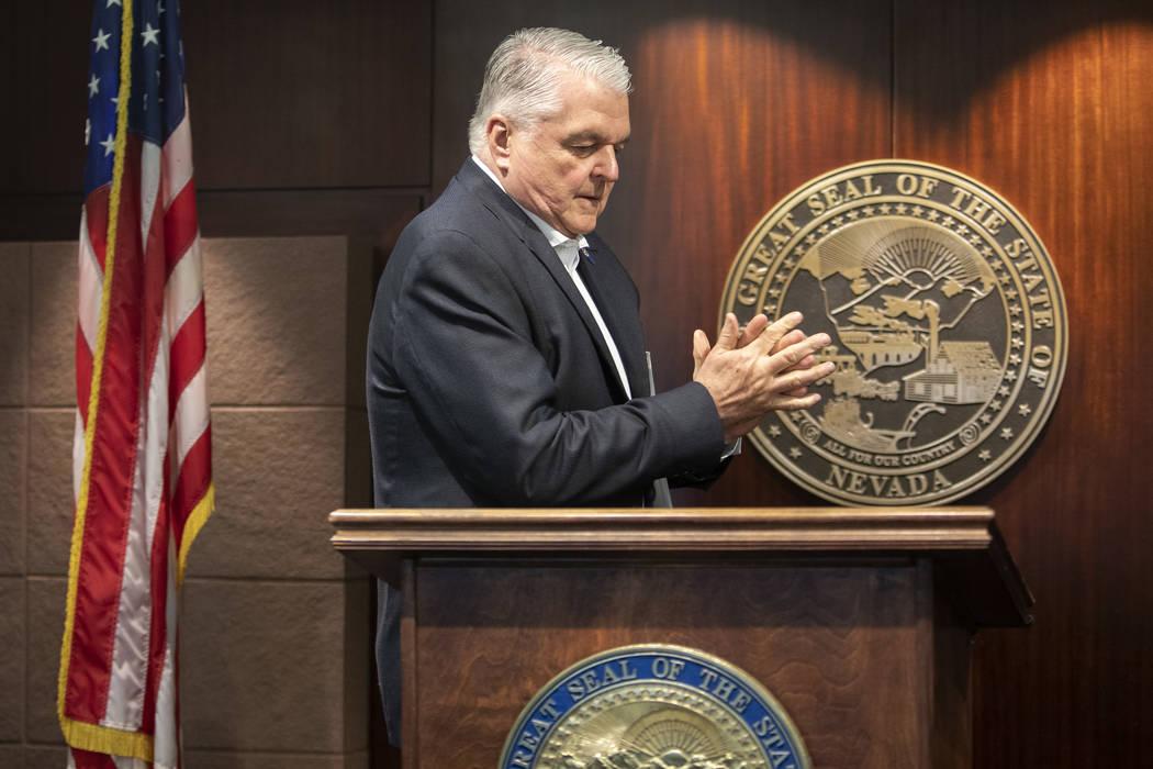 El Gobernador Steve Sisolak usa desinfectante de manos antes de una rueda de prensa sobre el nu ...