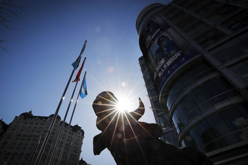 Una estatua de un toro, un icono de la inversión, se encuentra fuera de un edificio de oficina ...