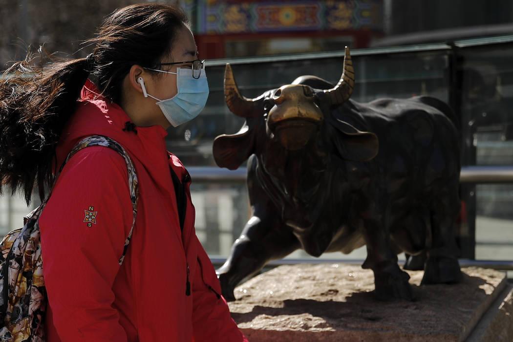 Una mujer con una mascarilla protectora camina por la estatua del toro, icono de las inversione ...