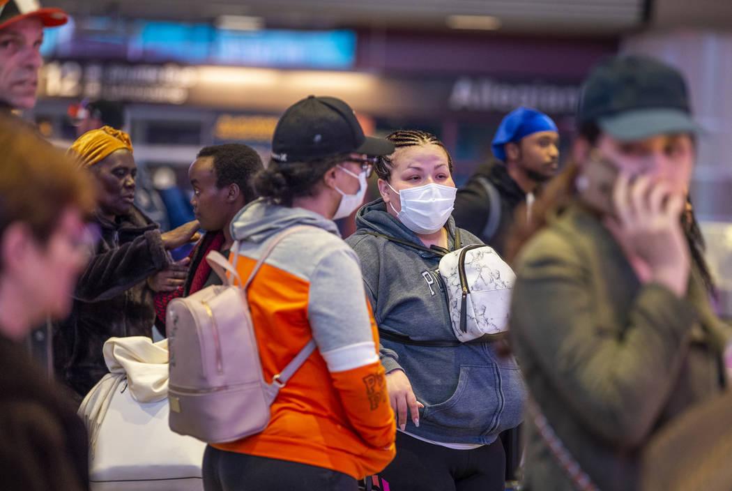 Las pasajeras Sherry Carter, izquierda, y Kimberly Thompson de Virginia, usan máscaras faciale ...