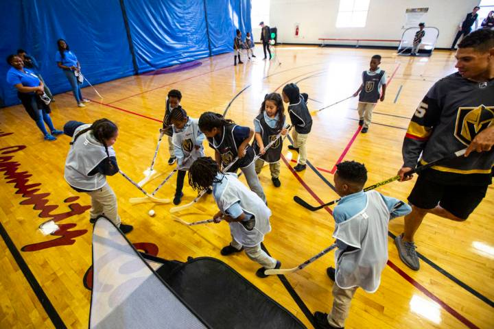 Los niños luchan por la pelota durante una clínica de hockey callejero para jóvenes en el Ce ...