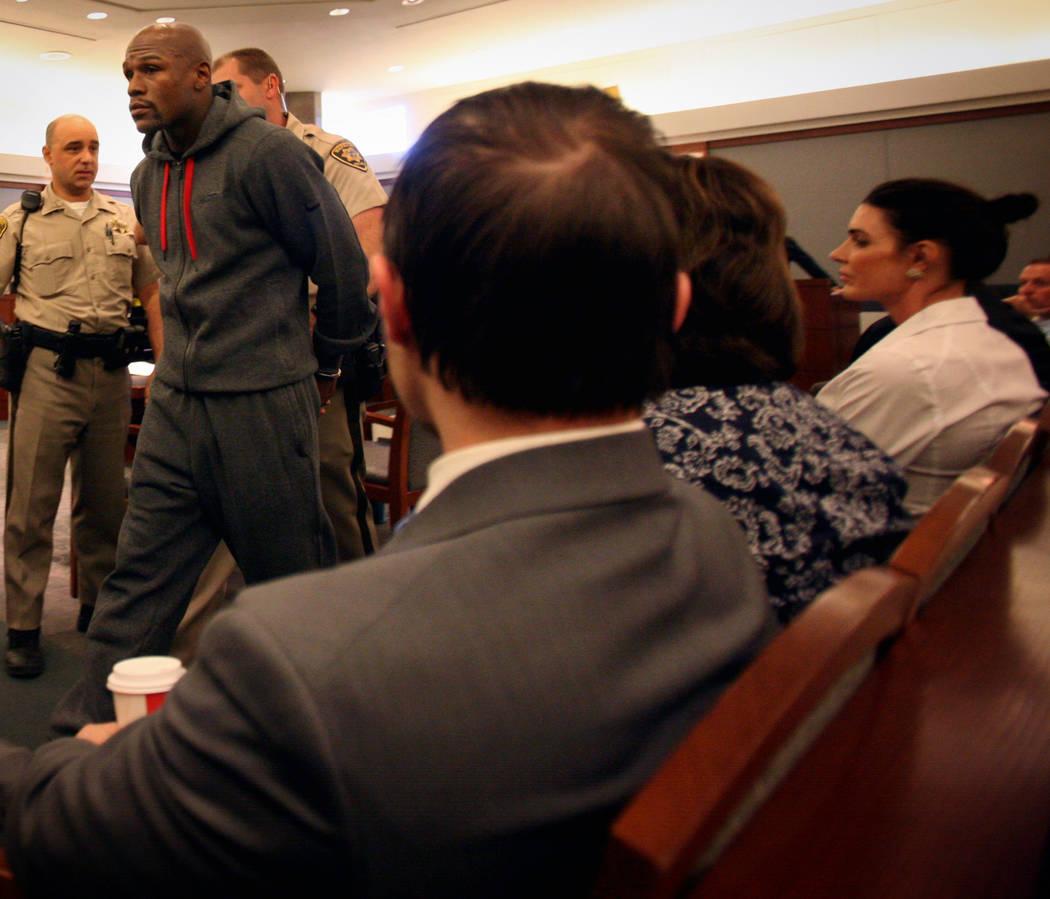 Los oficiales escoltan al boxeador Floyd Mayweather Jr. fuera de la sala del Centro Regional de ...