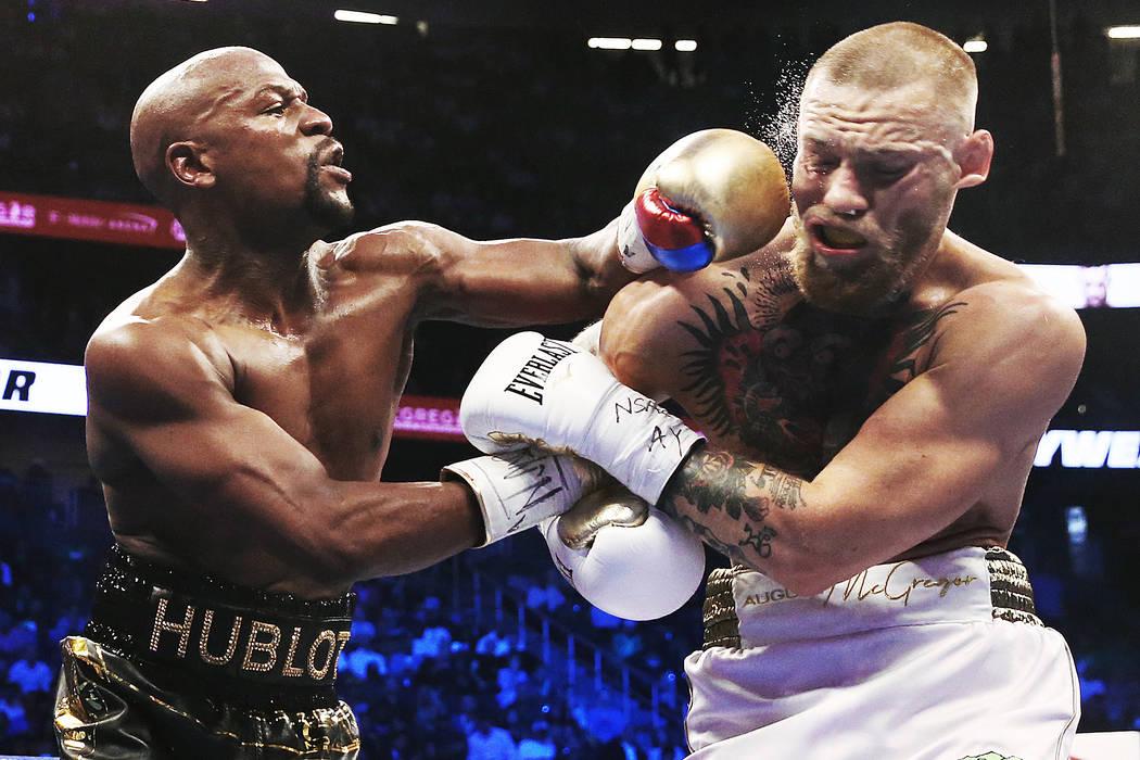 Floyd Mayweather, izquierda, lanza un gancho en la mandíbula de Conor McGregor el sábado, 26 ...