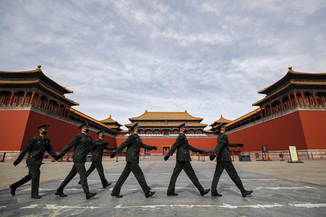 Soldados con máscaras protectoras marchan por las puertas cerradas de la Ciudad Prohibida, nor ...
