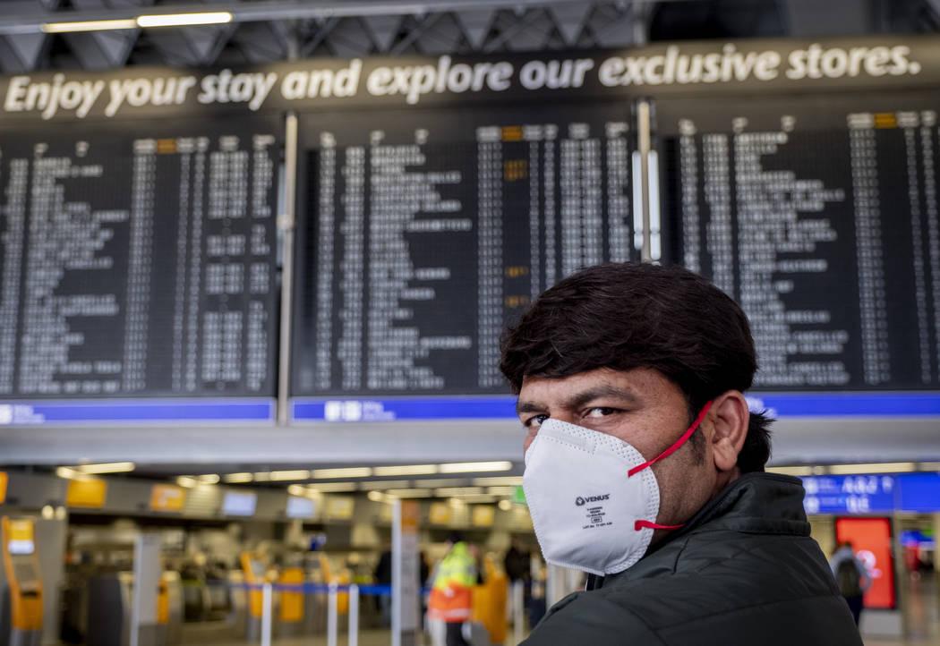 Un pasajero de la India espera su vuelo en una terminal del aeropuerto de Frankfurt, Alemania e ...