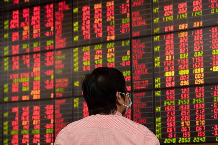 Un inversor tailandés revisa una pizarra electrónica que muestra los precios de las acciones ...