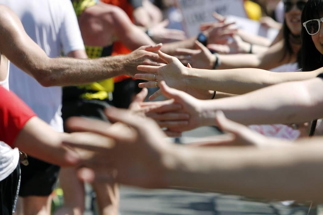 Esta foto del 12 de abril de 2012, muestra a los corredores chocando las palmas con los especta ...