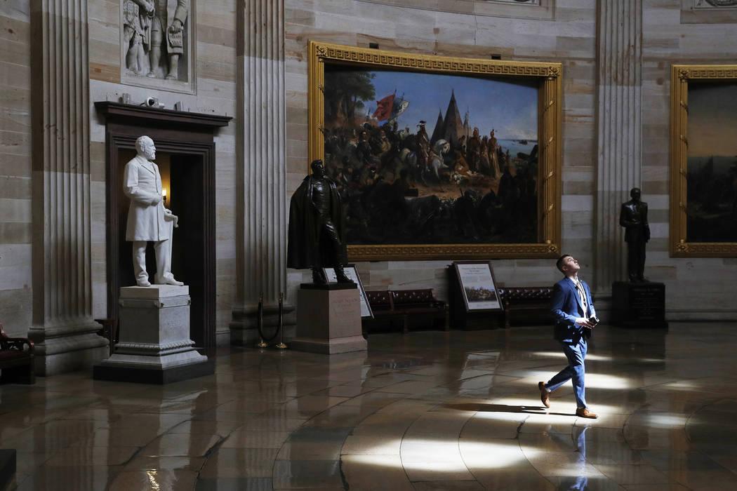 Un hombre camina por la rotonda vacía del Capitolio de EE.UU. el lunes, 16 de marzo de 2020. E ...