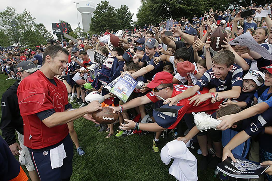 Tom Brady, de los Patriots de Nueva Inglaterra, izquierda, firma autógrafos para los aficionad ...