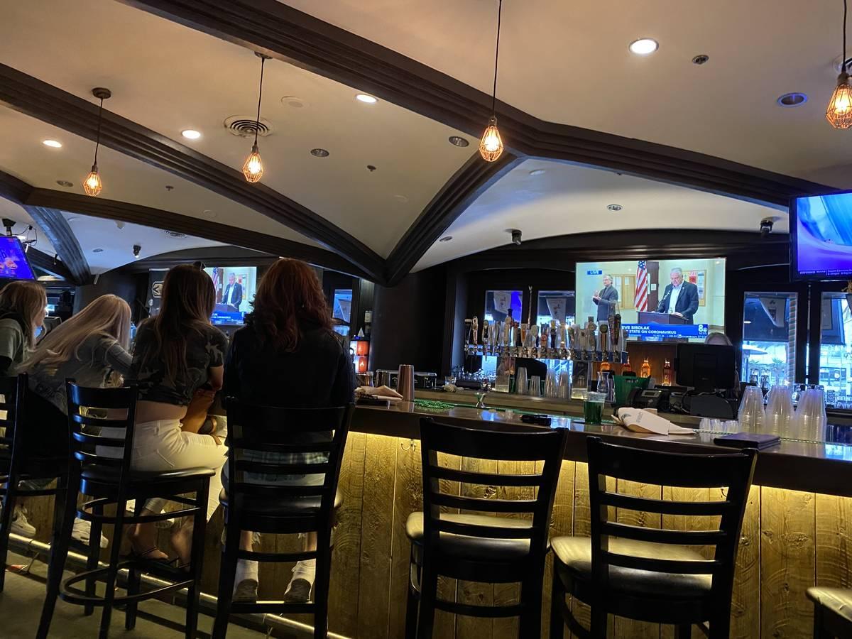 Shannon White (derecha) y sus tres hijas observan mientras el gobernador Steve Sisolak anuncia ...