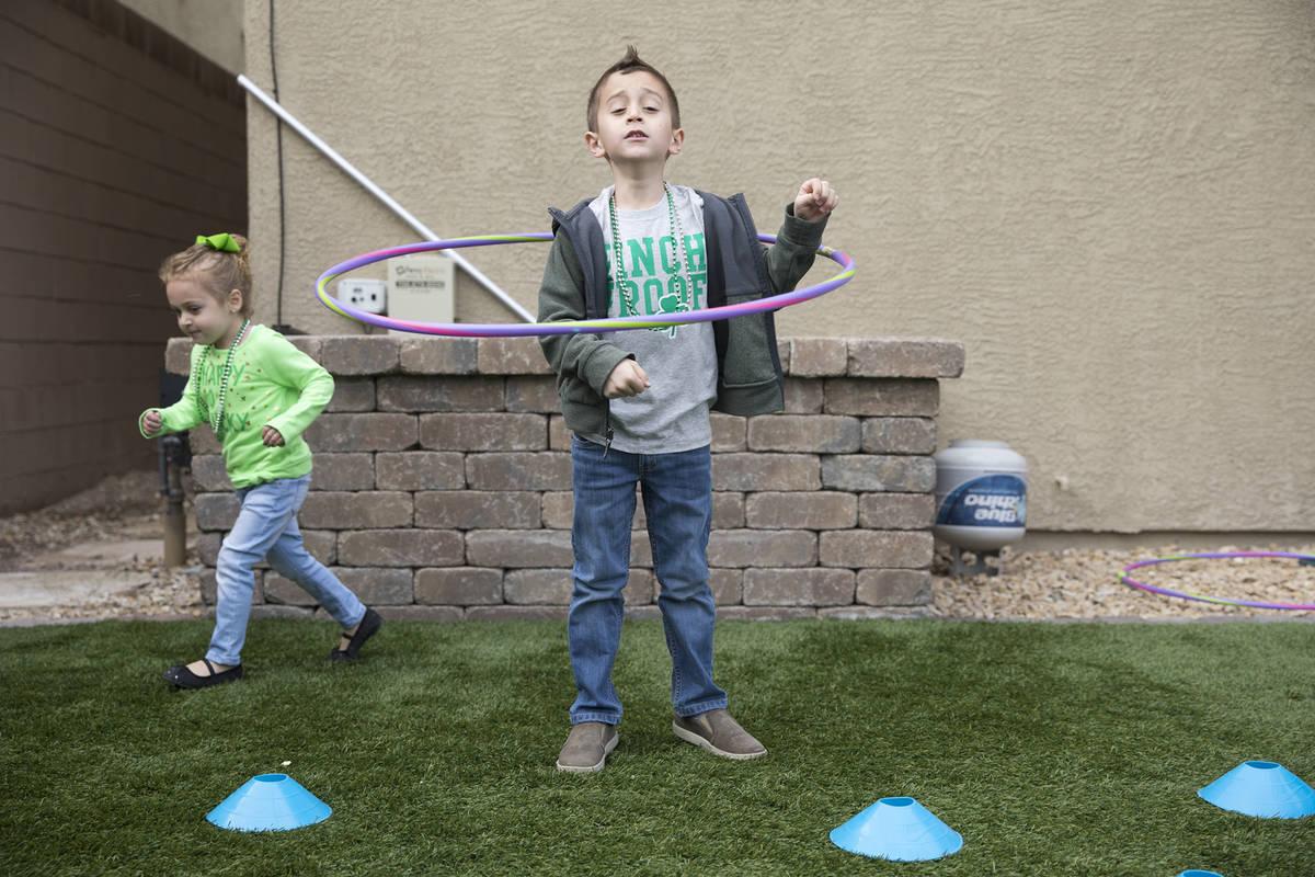 Alex Doleshal, 6, izquierda, juega con su hermana, Angie, 3, derecha, en su casa de Henderson e ...