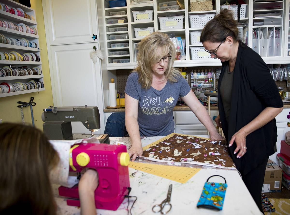 Anissa Gustafson, centro, muestra a su amiga Terri Yannone, derecha, cómo cortar tela para ela ...