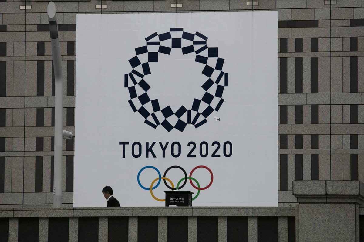 Un hombre pasa junto a una gran pancarta promocionando las Olimpiadas de Tokio 2020 en Tokio el ...