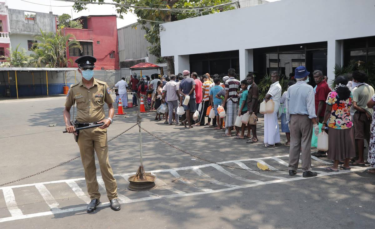 Los habitantes de Sri Lanka hacen fila para obtener queroseno mientras un agente de policía ha ...