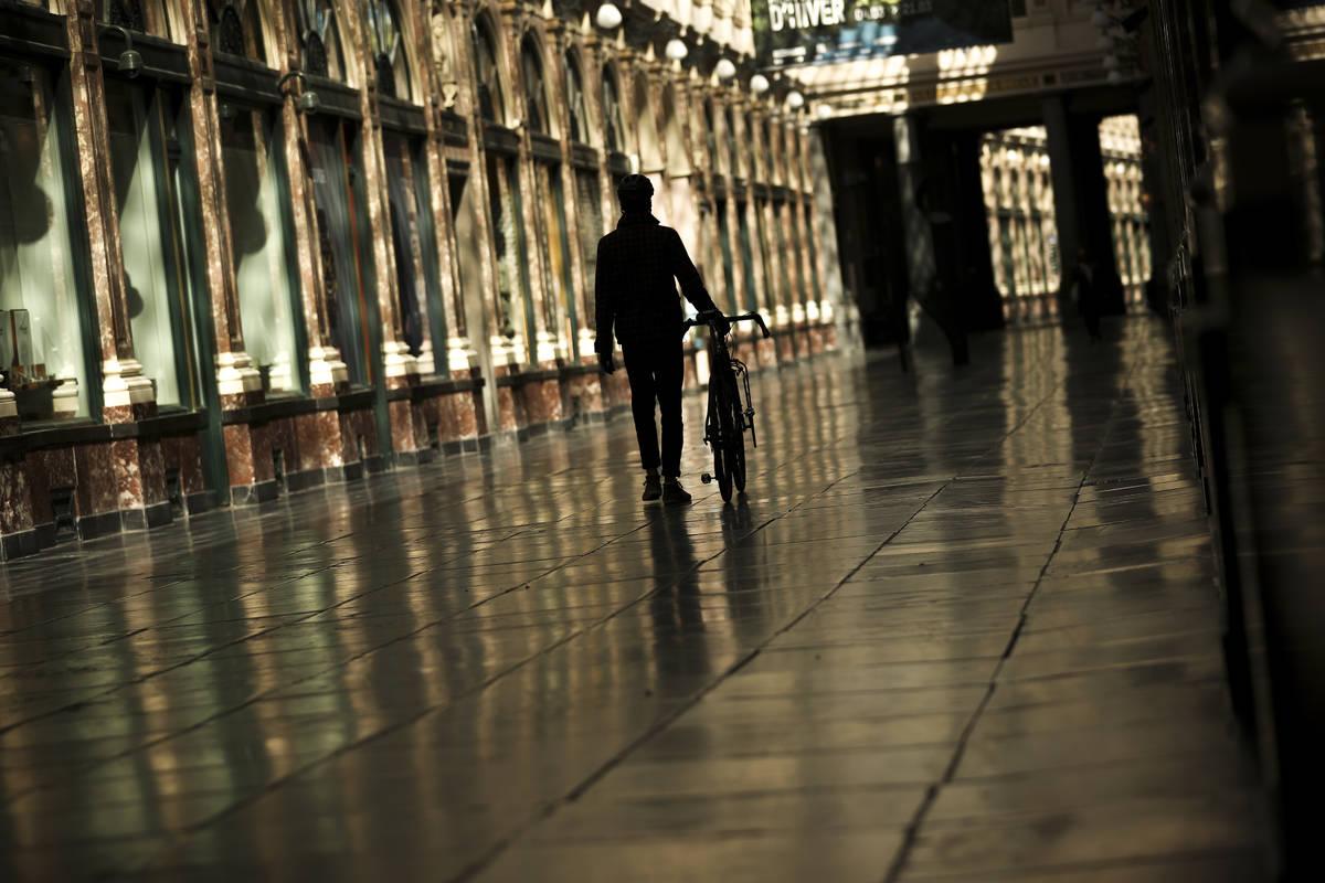 Un hombre camina a lo largo de una calle comercial prácticamente vacía de la Galería Real de ...