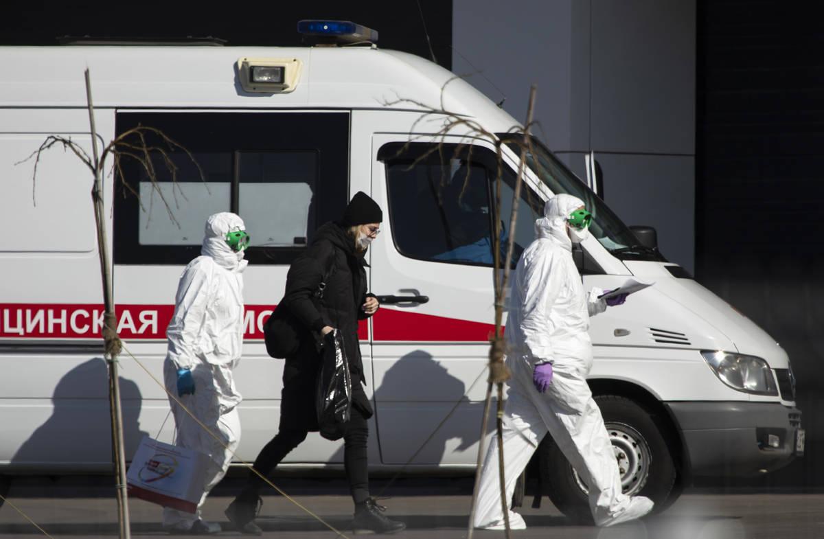 Trabajadores médicos escoltan a una mujer, sospechosa de estar infectada por coronavirus, para ...