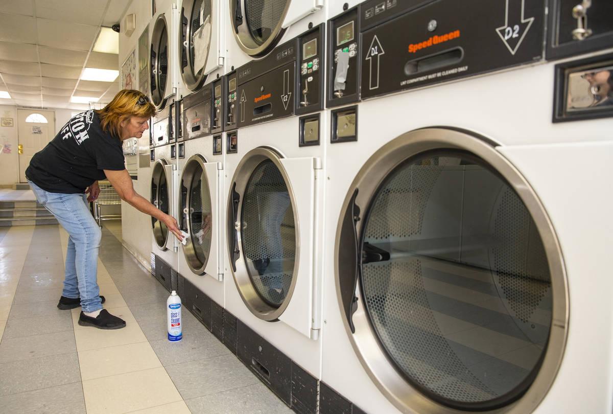 La gerente de la lavandería Bubbles 'n Bleach, Lynn Hess, desinfecta cada secadora el martes, ...