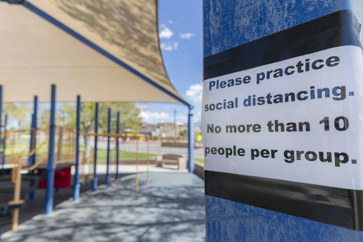 Un cartel pidiendo distanciamiento social se ve en un patio de recreo en el Veteran's Memorial ...