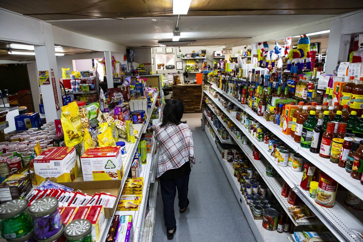 Sunny Martell, dueña de Martell Market, camina por un pasillo lleno de artículos almacenados ...