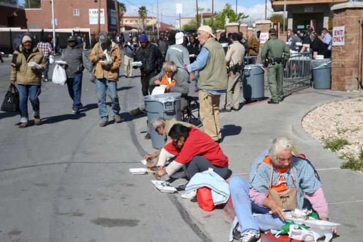 Gente come almuerzos para llevar de Catholic Charities en Foremaster Lane en Las Vegas el jueve ...