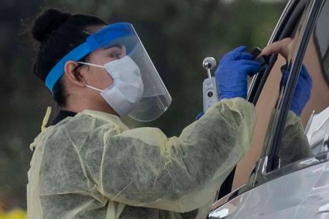 Un profesional médico de la UNLV lleva a cabo una prueba en la acera de un paciente que experi ...