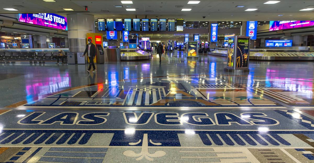 Un pasajero con un cubrebocas camina por el área de equipaje en la Terminal 1 del Aeropuerto I ...